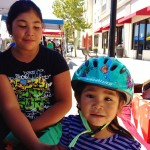 Greenfield girl helping little ones learn bike helmet fit 2012